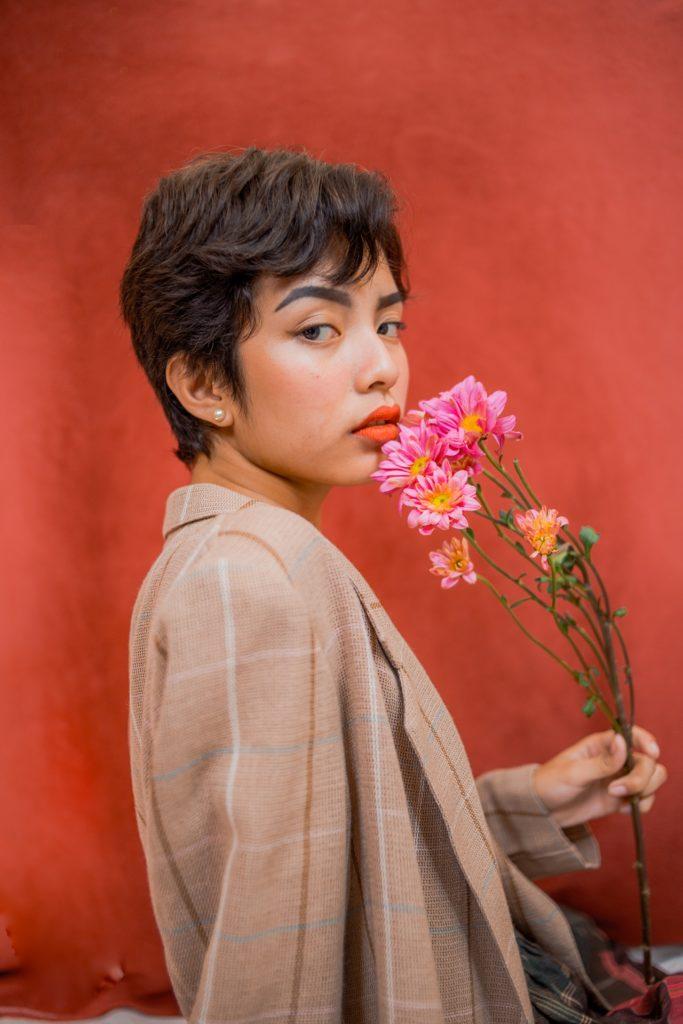 Frau mit Pixie Cut und Blumen